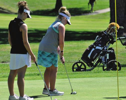 ISABELLE DOOLEY watches her kid sister, Karoline, putt as the girls play June 11 in their first-ever golf tournament. SHAWN RONEY | Staff