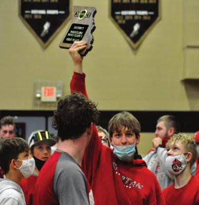 SENIOR RYKER PLYMELL hoists the Class 1 District 6 plaque after he and his fellow Spartans win the team title at Lathrop. SHAWN RONEY | Staff