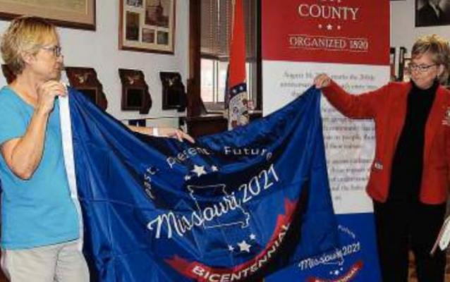 RAY COUNTY Clerk Glenda Powell, left, and Rep. Peggy McGaugh unfurl the state bicentennial celebration flag.