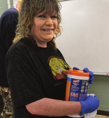 MAINTENANCE WORKER Rhonda Jones stands ready with approved disinfectant wipes.