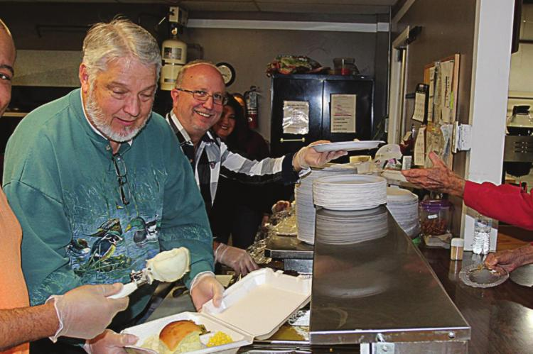 AT THE 2019 Thanksgiving Dinner, from left, Pastors Rance Williams, Eddie Birdsong and Phillip Powers work together to prepare a plate for Lloyd Walker. J.C. VENTIMIGLIA | Staff